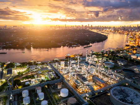 Aerial view of oil refinery near international port at night. Panorama of refinery plant at sunset. refinery factory and tank