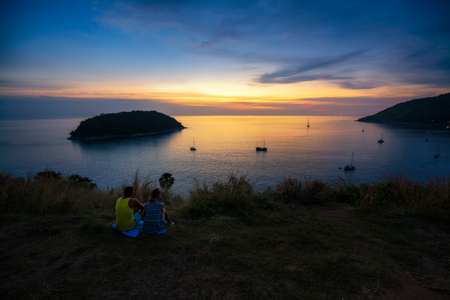 Romantic scene of middle aged love couple sitting on grass in view point look sunset at Promthep Cape Phuket, Thailand. Фото со стока