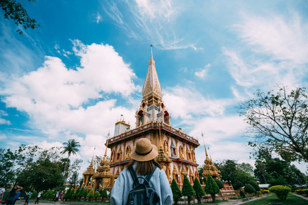 Young woman traveler with backpack traveling into beautiful pagoda in Wat Chalong or Chalong temple at Phuket town, Thailand. Its most popular thai temple in Phuket Thailand.
