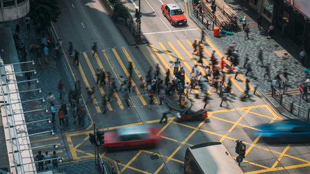 People and taxi cabs crossing a very busy crossroads in Tsim Sha Tsui district Hong Kong, China