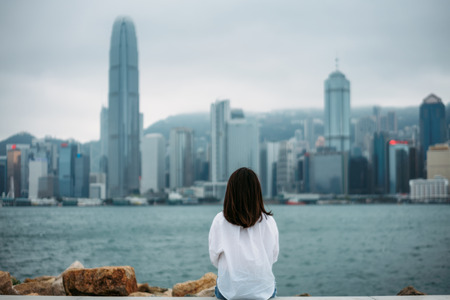 Young woman traveler is sitting looking cityscape view of Hong Kong China