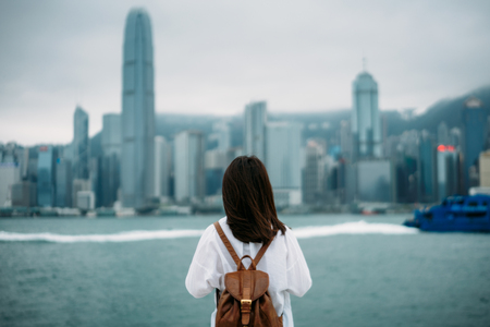 Young woman traveler is looking cityscape view of Hong Kong China