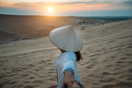 Mans hand holding hands of young woman traveler vietnamese traditional costume wearing Ao dai traveling into White Sand dunes at Mui ne in Vietnam at sunrise with beautiful sky