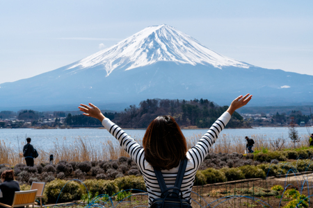 Young woman traveler looking view of mount fuji from lake kawaguchi side with happinest, Mt Fuji beautiful view from the lake kawaguchiko near Tokyo in Japan