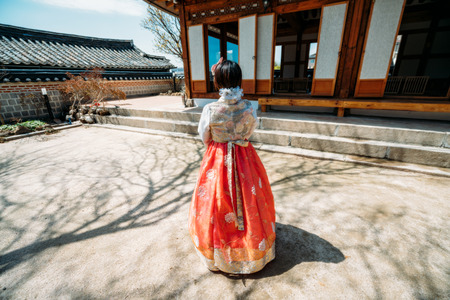 Young woman traveler in traditional korean dress or call hanbok traveling into Bukchon Hanok Village at Seoul city in South Korea Фото со стока