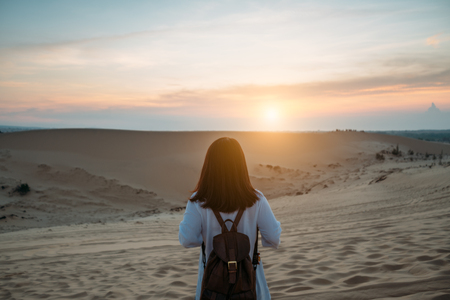 Young woman traveler traveling into White Sand dunes at Mui ne in Vietnam at sunrise with beautiful sky