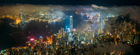 Panorama aerial view of Hong Kong City skyline at night over the clouds Фото со стока
