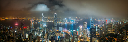 Panorama aerial view of Hong Kong City skyline at night over the clouds Редакционное