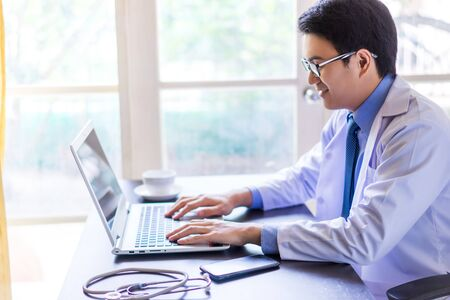Young asian handsome doctor using his laptop computer with happiness Stock fotó - 144559810