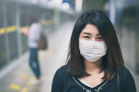 Young asian woman wearing protective face mask in subway due to the polluted air or pm 2.5 and Coronavirus disease or COVID-19 outbreak situation in all of landmass in the world.