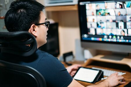 Young asian business man using computer for a online business meeting with his colleagues about plan in video conference. back view of business man have webcam group conference with coworkers at home Stock fotó - 147260153