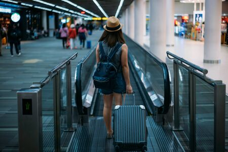 Young woman traveler in international airport with backpack holding suitcase or baggage in her hand, Beautiful young tourist girl with backpack and carry on luggage in airport terminal, on travelator