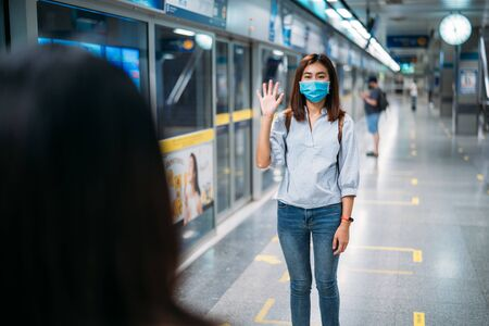Two young asian women friends wearing protective mask meet in a subway station with bare hands. Instead of greeting with a hug or handshake due to Coronavirus disease or COVID-19 outbreak situation