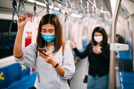Young asian woman wearing protective face mask using smartphone in underground train due to the polluted air or pm 2.5 and Coronavirus or COVID-19 outbreak situation in all of landmass in the world. 写真素材