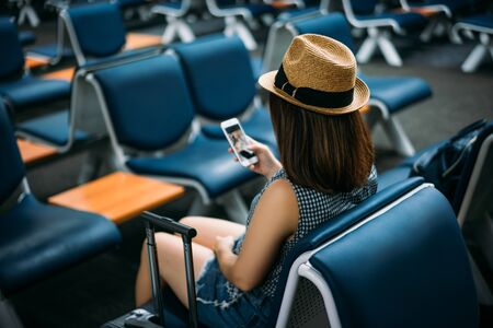Young woman traveler sitting while using smartphone on chair of passenger in an airport lounge waiting for flight aircraft at international airport