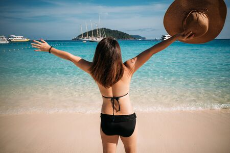 Rear view of young woman traveler with black bikini lifting two hand  on the beach at similan islands in Andaman sea at Phang Nga province near Phuket and Krabi in southern of Thailand. Summer Relax