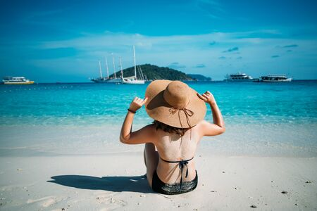 Rear view of young woman traveler with hat relaxing on the beach at similan islands in Andaman sea at Phang Nga province near Phuket and Krabi in southern of Thailand. Summer Relax Stock fotó - 147260665