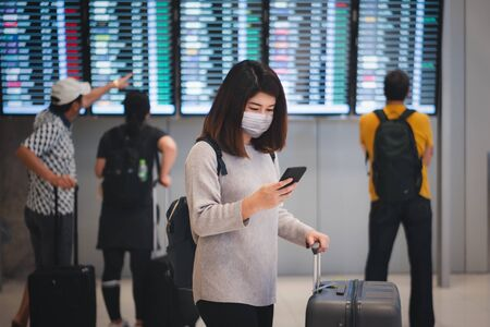 Young asian woman traveler using smartphone and holding luggage while waiting check-in at terminal in international airport due to Coronavirus or COVID-19 outbreak situation in the world 写真素材