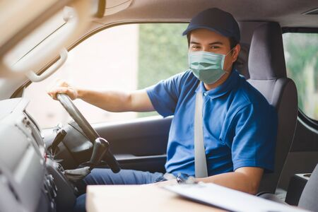 Young asian delivery man wearing protective face mask driving his van with packages on the front seat due to Coronavirus disease or COVID-19 outbreak situation in all of landmass in the world.