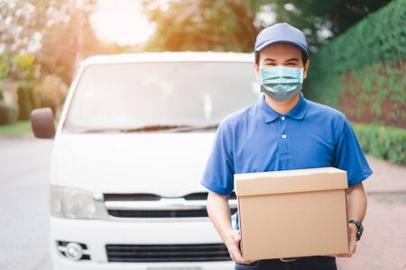 Postal delivery courier man wearing protective face mask in front of cargo van delivering package holding box due to Coronavirus disease or COVID-19 outbreak situation in all of landmass in the world. 写真素材