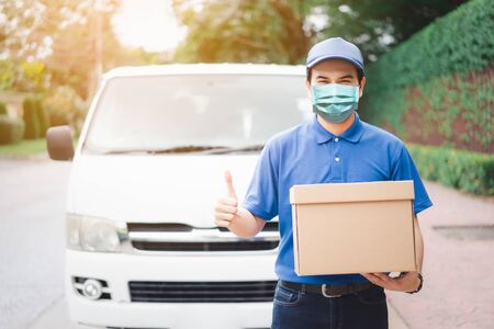 Postal delivery courier man thumbs up wearing protective face mask in front of cargo van delivering package holding box due to Coronavirus disease or COVID-19 outbreak situation in all of landmass in the world. 写真素材