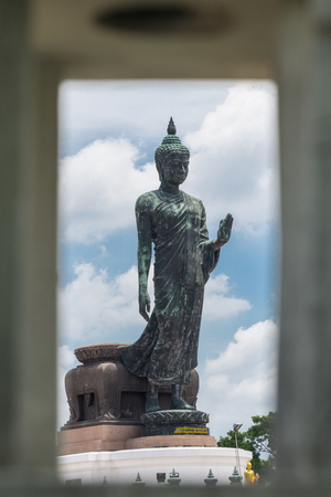Large Bronze statue Walking Buddha with Frame Look through from Street Light Thailand Travel Concept.