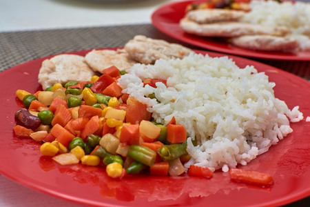 satisfying: Vegetables with rice and chicken on a red plate