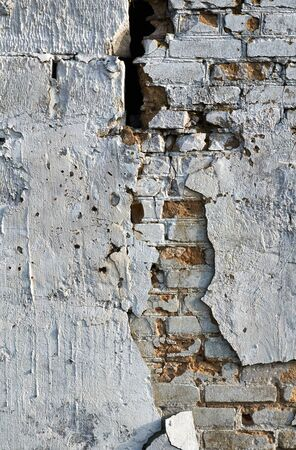 gaping: brick wall with a gaping black hole and cracked plaster