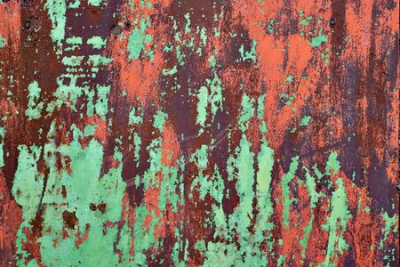 Rusty metal plate painted in green and red colors