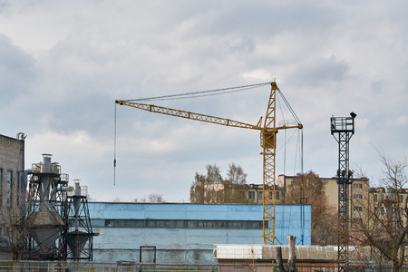 slings: tower crane on a background of machine-building plant