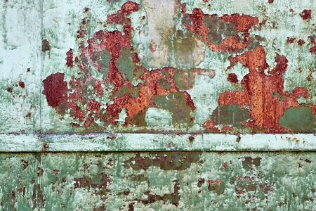 rust covered: Close Up texture of Chipped peeling green paint over rust, covered with crumbling Paint