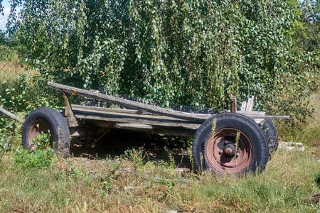 carreta madera: viejo entró en mal estado de carro de madera de pie en el patio trasero en el fondo de los árboles de abedul