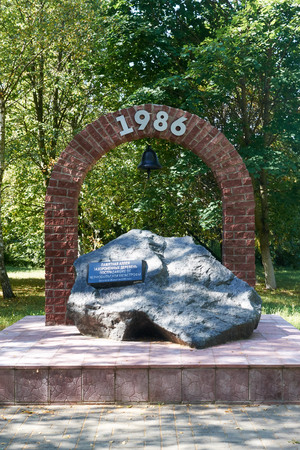 chernobyl: monument to Chernobyl victims in the form of a stone arch with a bell and black name plate