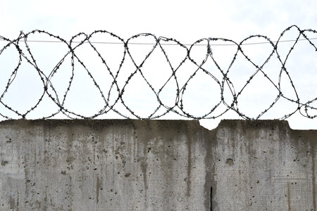 barbs: barbed wire on concrete fence on the background of cloudy sky
