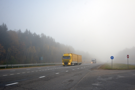 Truck is driving along the road in the morning in a thick fog Stock Photo