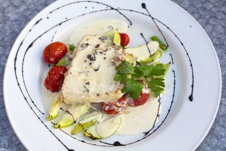 Pike perch fillet with creamy nut sauce with zucchini and grilled tomatoes