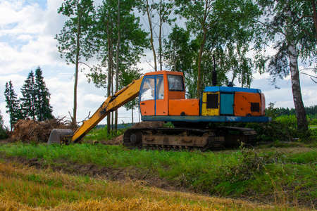 Excavator uproots trees to expand agricultural fields. The bulldozer harms the environment as a result of human activity. Ecology problem.