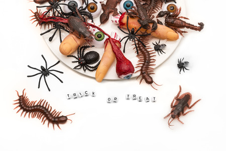 Trick or treat words surrounded by candy bugs, joke plastic fingers and eyeballs on an overflowing dish onto a white background.Could work great as an kids party invitation.