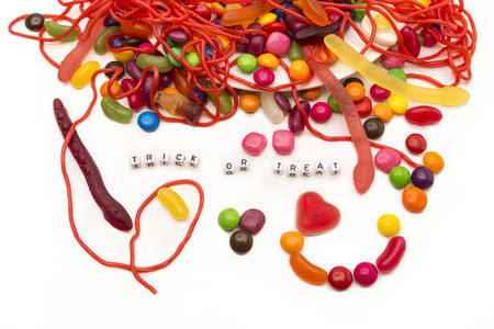 Trick or treat words surrounded by colouful candy beans, strings and worms from an overflowing dish onto a white background.Could work great as an kids party invitation.