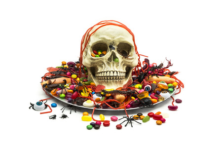 A candy dish filled with trick or treat candy, plastic bug toys and skull on white