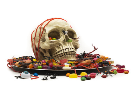 Halloween party food - trick or treat candy on a plate with a skull center piece. The tricks are toy bugs, rubber fingers and eyeballs.The treats are colorful candy, jelly snakes, chocolate shells and jellybeans.