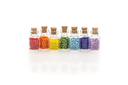 Tiny glass bottles with a cork stopper, filled with a rainbow colours of beads, on a white background