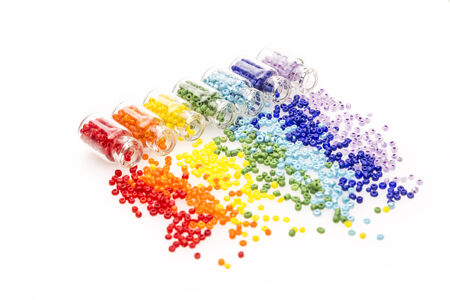 Tiny glass bottles filled with a rainbow colours of beads spilling out, on a white background Imagens