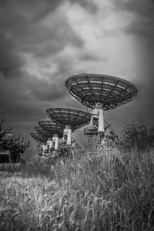 radio telescope: Radio telescope satellite dish array in a barley field before a storm in black and white
