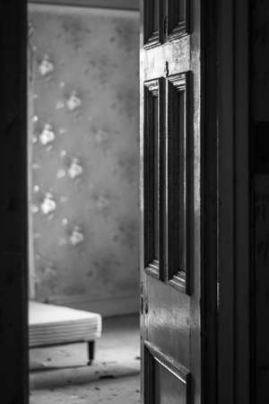 Monochrome image of an open door with missing door knob and an old room beyond