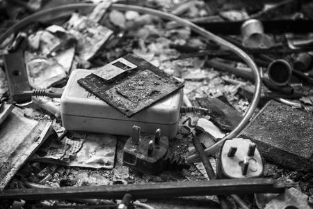 Floppy disk, mains lead with UK 3 pin plug, power supply transformer, burnt documents and other office items after a fire