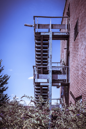 Red brick and concrete office building, with a rusty fire escape. Abandoned and derelict under a blue sky. Imagens