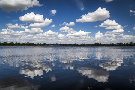 Reflections of white fluffy clouds in a lake on a blue, sky, sunny day