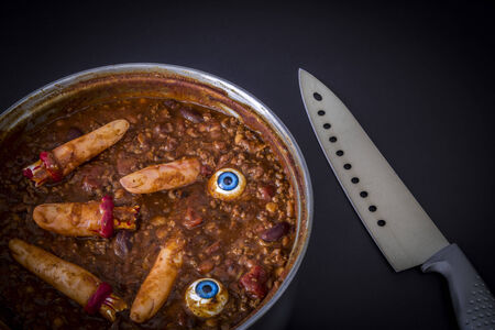 Halloween humour - chili cooking with fake fingers and eyeballs. Great as a halloween or murder-mystery dinner invitation. Imagens