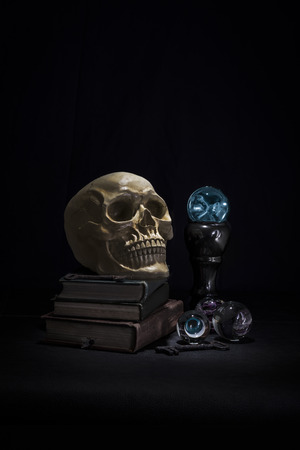 Dark and shadowy human skull resting on old books in a pool of light. Crystal ball is glowing blue.
